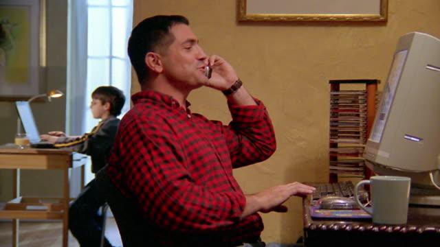 medium shot man talking on phone at computer / son on his own computer in background - コードレスフォン点の映像素材/bロール