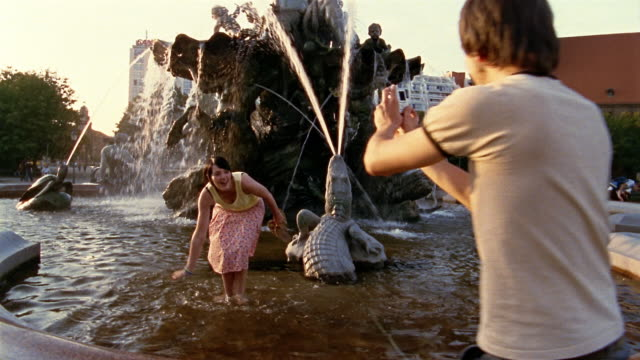 medium shot man talking photo of woman splashing water in fountain / berlin, germany - water fight stock videos & royalty-free footage