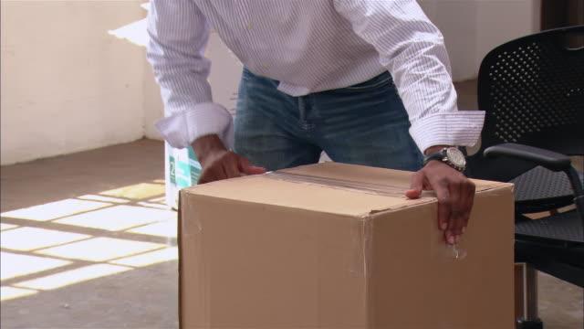Medium shot man taping box closed in loft space/ Brooklyn, New York