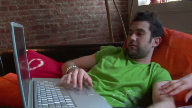 medium shot man typing on laptop as couple lies on couch/ new jersey - stoppelbart stock-videos und b-roll-filmmaterial