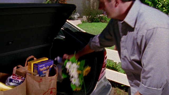 medium shot man unpacking groceries from car trunk with girl and woman watching next to house in background / california - boot stock videos & royalty-free footage