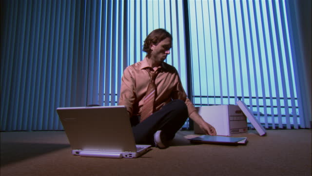medium shot man using laptop and sitting cross-legged on office floor - cross legged stock videos & royalty-free footage