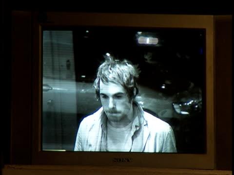 Medium shot man viewed through surveillance monitor looks around and departs