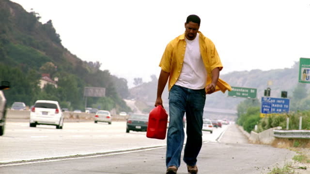 medium shot man walking along shoulder of route 2 carrying gas can / glendale, california - vehicle breakdown stock videos and b-roll footage
