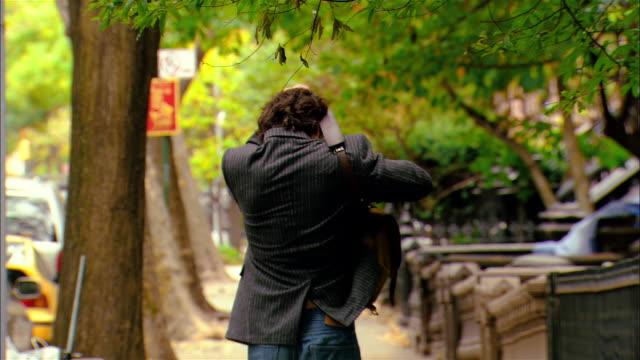 Medium shot man walking down street/ Brooklyn, New York