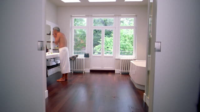 vídeos de stock e filmes b-roll de medium shot man walking out of shower, wearing towel in bathroom / drying face and hair w/windows + trees in background - toalha