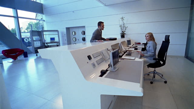 vidéos et rushes de medium shot man walking up to reception desk / woman making phone call and directing him / berlin - accueil entreprise