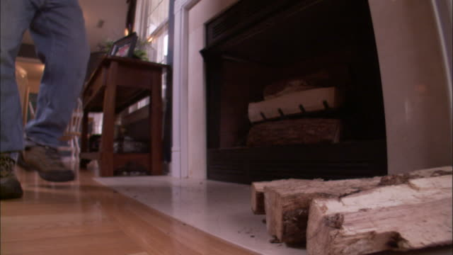 Medium Shot - Man walks over and places chopped firewood next to fireplace /