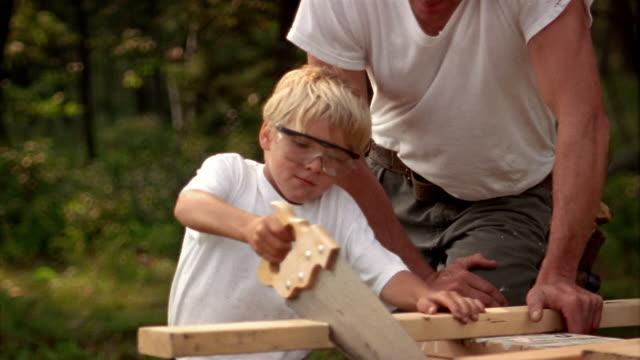 Medium shot man watching as boy wearing goggles saws board