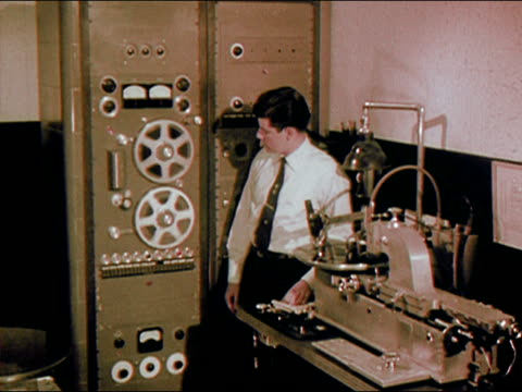 vídeos de stock, filmes e b-roll de 1956 medium shot man watching audio reels spin/ man looking into microscope/ audio - microscópio