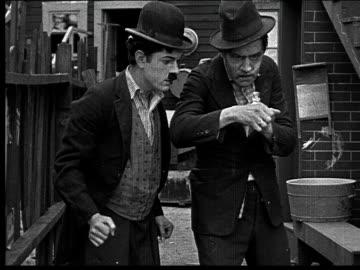 stockvideo's en b-roll-footage met 1918 b/w medium shot man watching man snort large amount of cocaine (or snuff?) off of hand in alley - drug gefabriceerd object