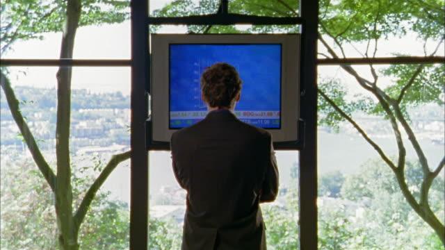 medium shot man watching tv screen w/financial info / turning and facing cam w/arms folded - aktiemarknadsdata bildbanksvideor och videomaterial från bakom kulisserna
