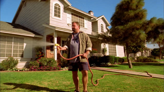 medium shot man watering lawn w/hose / water on cam / phoenix, arizona - prato rasato video stock e b–roll
