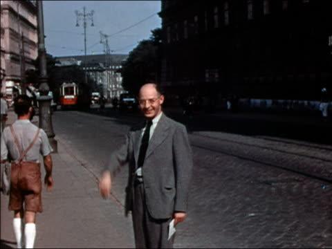 medium shot man waving and walking toward cam / smiling + saluting / vienna - 1938 video stock e b–roll