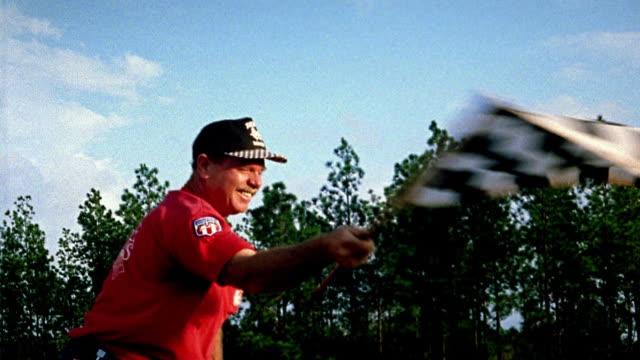 vídeos de stock e filmes b-roll de medium shot man waving checkered flag at race track / alabama - quadriculado