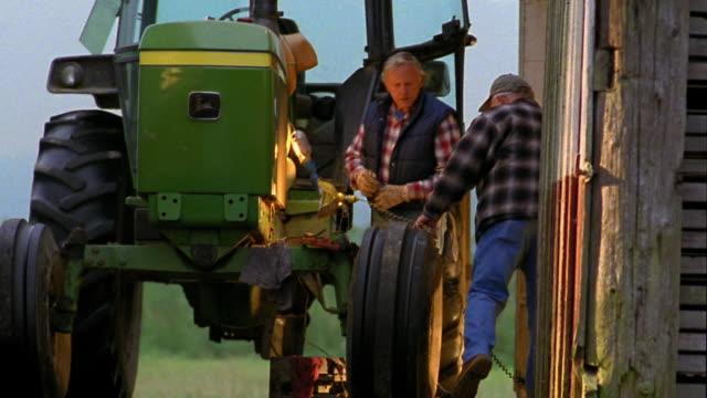 medium shot man w/baseball cap walking toward tractor and man beside it /two men examining tractor - baseball cap stock videos & royalty-free footage