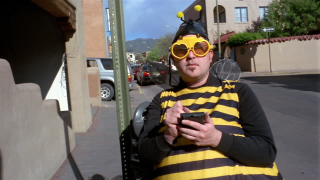 Medium shot man wearing bee costume using personal hand held device