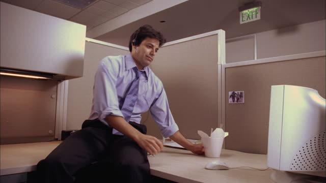 vídeos y material grabado en eventos de stock de medium shot man w/headphones eating chinese food and using computer in office cubicle - shirt and tie