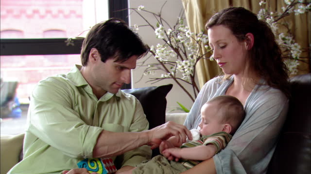 Medium shot man wiping mouth of baby sitting on woman's lap