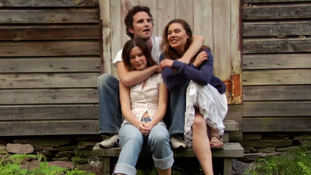 medium shot man with arm around woman sitting in front of barn / reaching over to hug other woman - maschio con gruppo di femmine video stock e b–roll