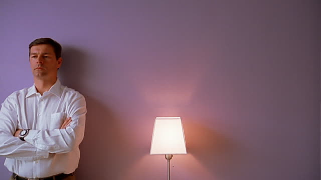 Medium shot man with arms crossed against wall next to lamp