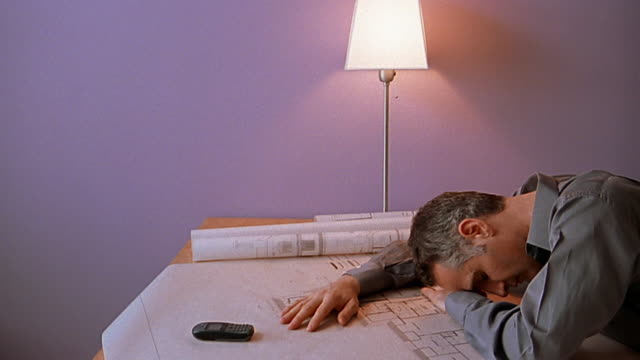 Medium shot man with head down on top of blueprints on desk