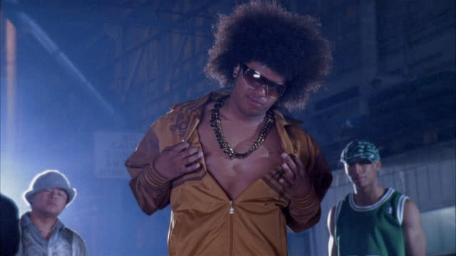 Medium shot man with large afro posing and dancing in warehouse
