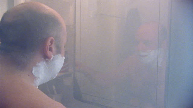 Medium shot man with shaving cream on face cleaning mirror in steamy bathroom / talking to himself and shaving