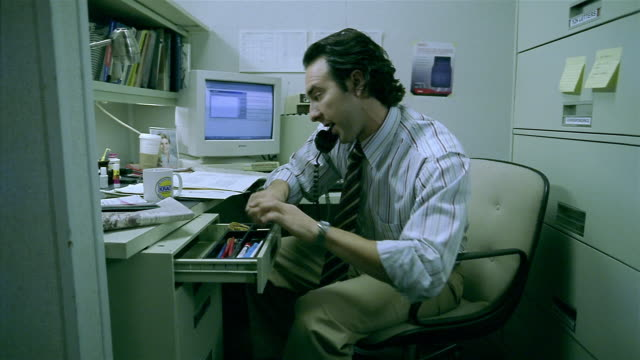 medium shot man working in cubicle / answering phone / looking up information in books and on computer - drawer stock videos and b-roll footage