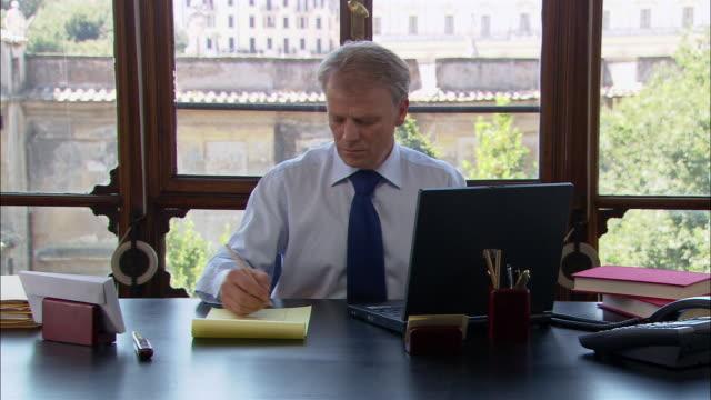 vídeos y material grabado en eventos de stock de medium shot man working on laptop at desk/ man taking notes from screen/ man typing/ rome - vestimenta de negocios formal