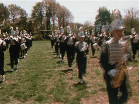 1970 medium shot marching band in moving in columns on football field - conformity stock videos & royalty-free footage