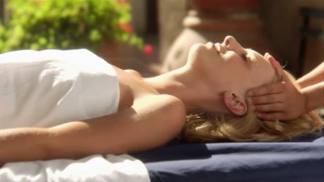 medium shot masseuse massaging woman at spa/ italy - massagetisch stock-videos und b-roll-filmmaterial