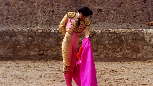 medium shot matador twirling his cape around / switching it from hand to hand behind his back - bullfighter stock videos & royalty-free footage