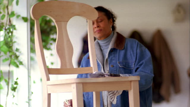 Medium shot mature Black woman applying varnish to wooden chair w/brush