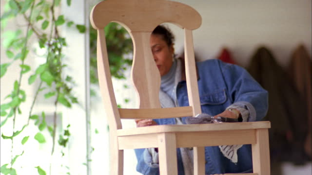 Medium shot mature Black woman applying varnish to wooden chair w/brush