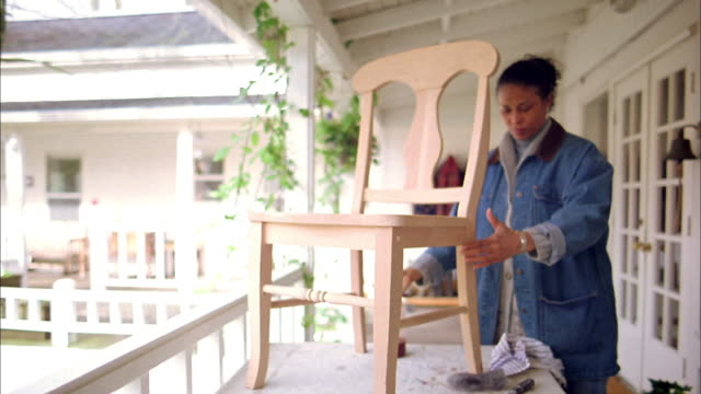 medium shot mature black woman examining and  varnishing a wooden chair w/brush on balcony - 50 59 years stock videos & royalty-free footage