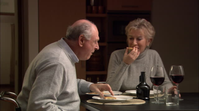 vidéos et rushes de medium shot mature couple eating bruschetta at dinner table / toasting glasses of red wine and drinking - quinquagénaire