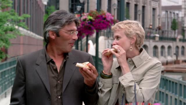 medium shot mature couple eating pizza and talking while walking along riverwalk / milwaukee, wisconsin - knob stock videos & royalty-free footage