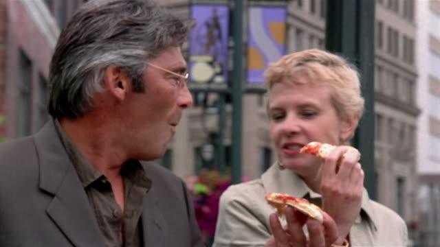 Medium shot mature couple eating pizza while walking along RiverWalk / sharing slices / Milwaukee