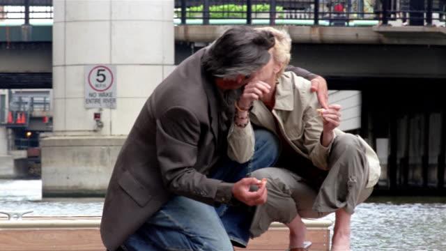 medium shot mature couple hugging while feeding ducks at river's edge / milwaukee, wisconsin - 恋に落ちる点の映像素材/bロール