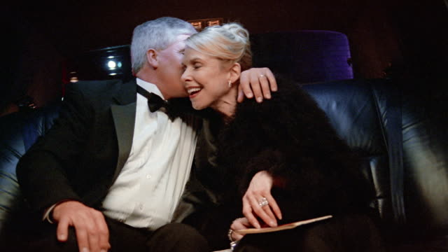 Medium shot mature couple in formalwear riding in limo / woman caressing man's hand
