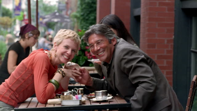 Medium shot mature couple leaning across table at sidewalk cafe, holding hands and smiling at CAM / Milwaukee