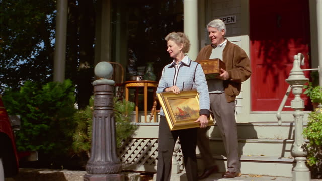 vidéos et rushes de medium shot mature couple leaving antique store with purchases / walking to 1948 willy's jeepster - brocante