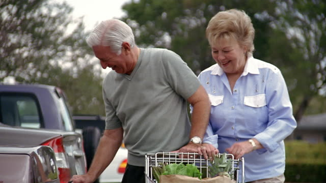 Medium shot mature couple putting groceries in trunk of car