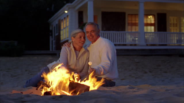 medium shot mature couple sitting on beach and roasting marshmallows by bonfire at night - beach house stock videos & royalty-free footage