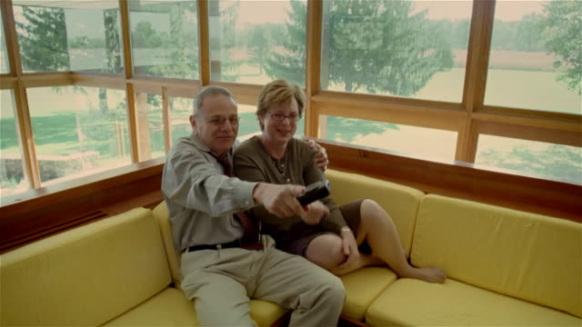 stockvideo's en b-roll-footage met medium shot mature couple sitting on couch, getting excited about what they see on television/ solebury, pennsylvania - overhemd en stropdas
