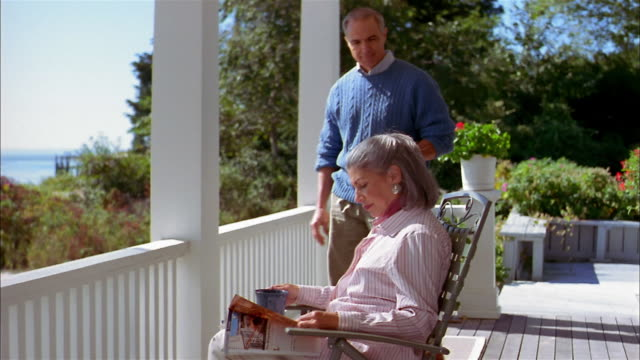 Medium shot mature couple sitting on house porch and drinking from coffee cups