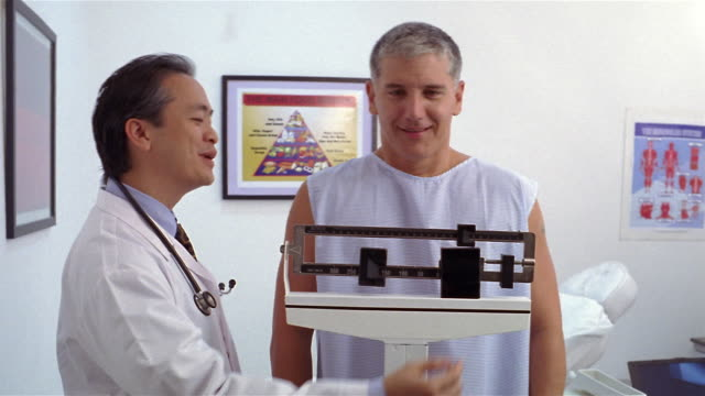 medium shot mature doctor weighing patient on scale and smiling/ panama city, panama  - dieting stock videos and b-roll footage