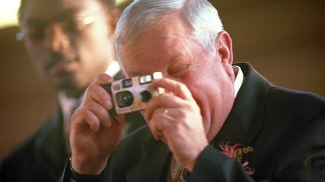 Medium shot mature man turning and snapping picture