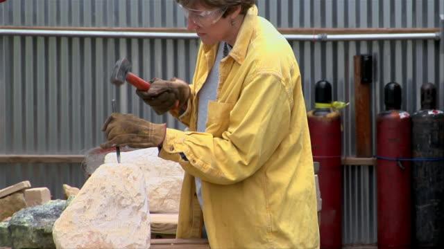 vidéos et rushes de medium shot mature woman sculpting stone outside studio/ san antonio, texas, usa - sculpteur